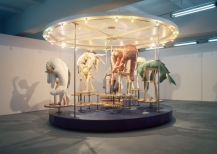 Stephen Wilks, Donkey Roundabout, diameter 500cm, hight 350cm, steel structure, motorised rotating platform, colored bulbs and spotlights, wood cogs, hand sewn textile donkeys, wood figures, 2008